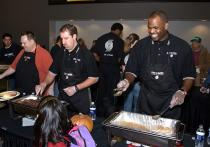Nate McMillan smiles and serves turkey at the Harvest Dinner.jpg