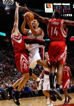Brandon Roy goes up and under between two Rockets players.JPG