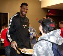 Greg Oden smiles as he helps out at the Harvest Dinner 2009.JPG