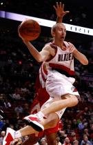 Steve Blake jumps in the air and throws a pass against the Rockets.JPG