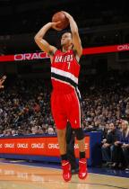 Brandon Roy sticks out his tongue and leans into a jumper in red sneakers.JPG
