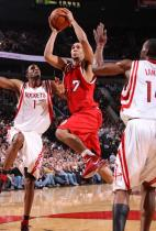Brandon Roy in a red retro Trailblazers jersey drives between two Rocket players.JPG