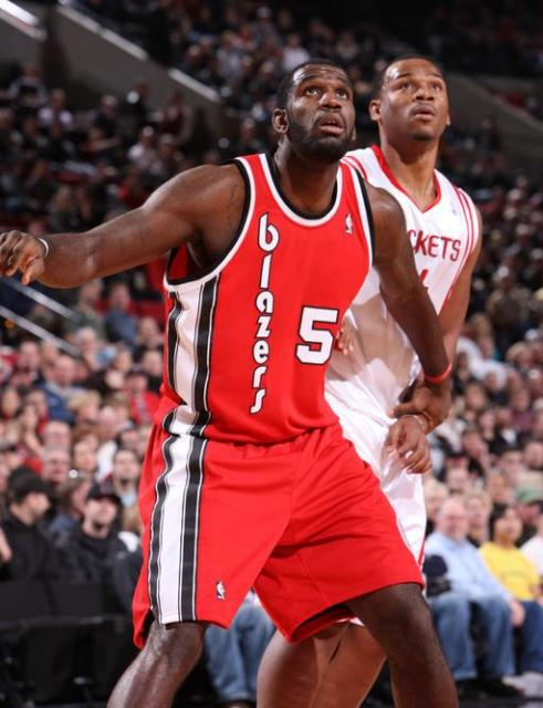 Greg Oden in a red Blazers jersey boxes out Chuck Hayes.JPG