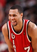 Brandon Roy is amused in a red retro Trail Blazers jersey.JPG
