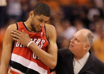 Nicholas Batum grabs his injured right shoulder.JPG